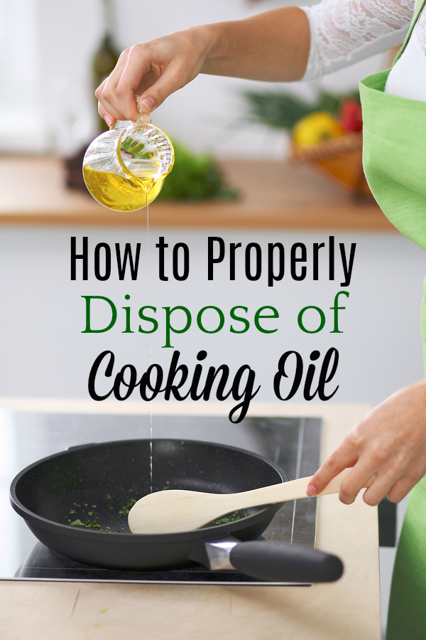 Young woman cooking in the kitchen while adding olive oil.