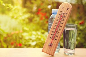 Thermometer on summer day showing high temperature