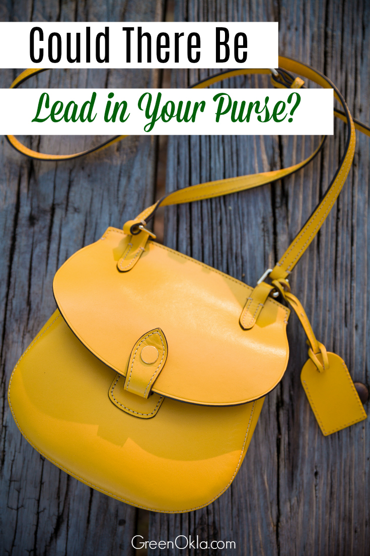 Top view on yellow purse on the old wooden table background. Nice woman's bag.