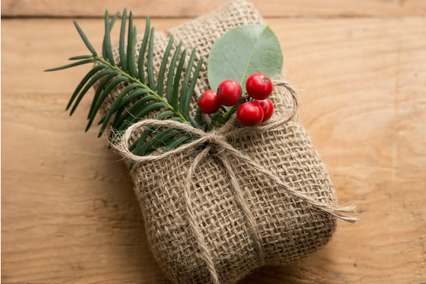 christmas box wrapped in burlap and some greenery