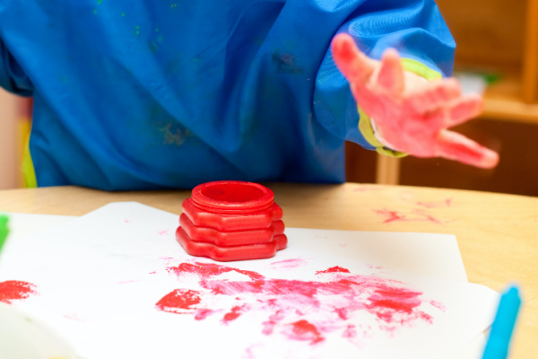 young child playing with red homemade finger paint
