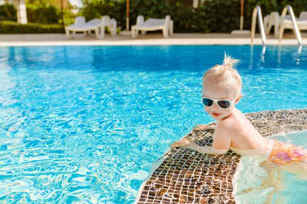 little baby with sunglasses swimming in the pool
