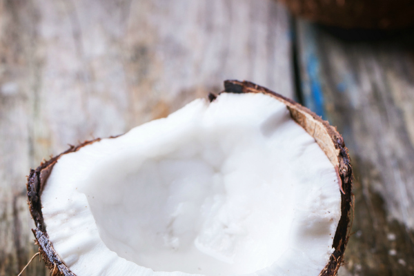 Broken coconut on old wooden background