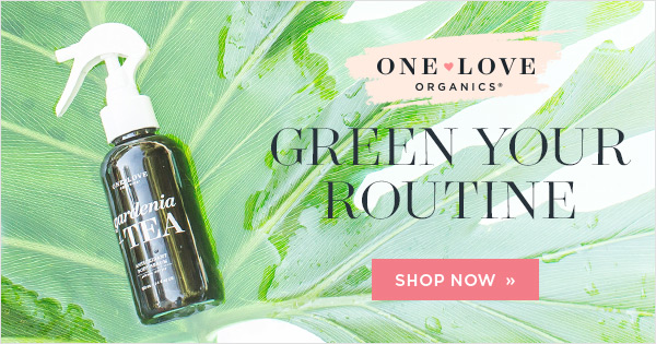 bottle of One Love Organics skin care on background with green leaves