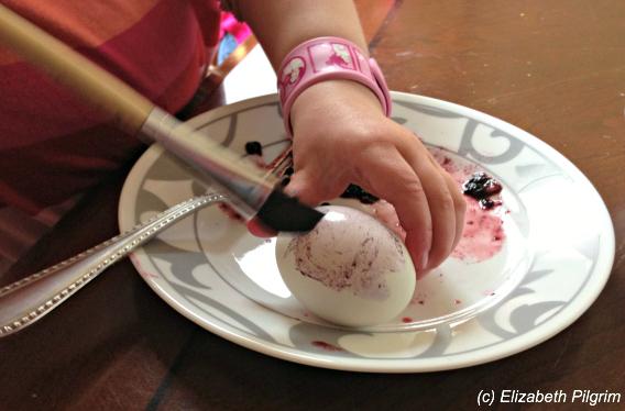 child painting easter egg