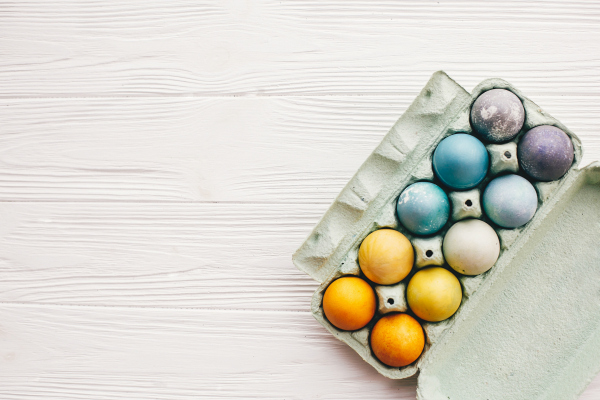 easter eggs in carton tray on white wooden background