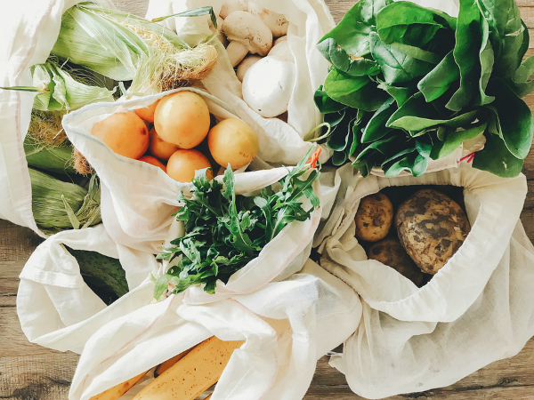 fresh vegetables in eco cotton bags used to avoid plastic on table in the kitchen. lettuce, corn, potatoes, apricots, bananas, rucola, mushrooms from market.