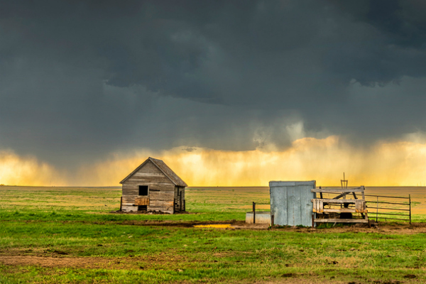 A mezocyclone storm with dark, gray clouds forming over the plains in Tornado Alley, Oklahoma at sunset