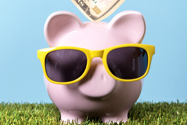 Hand putting a ten dollar bill into a pink piggy bank with sunglasses grass and blue sky