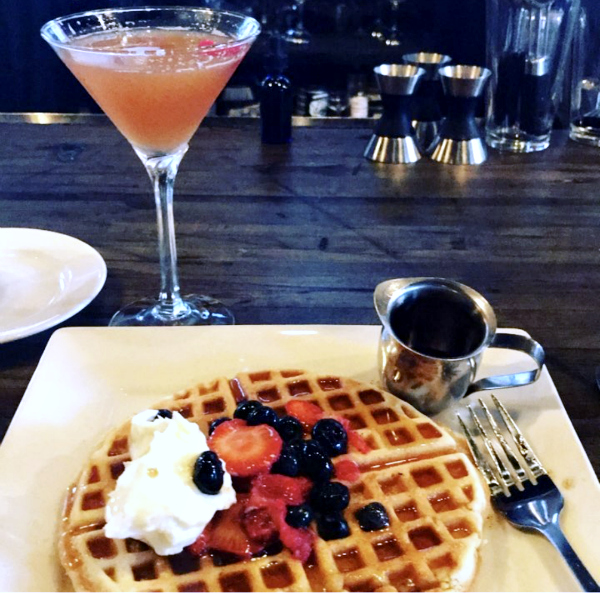 waffle with berries, whipped cream and a pink cocktail