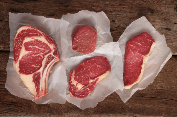 steaks on wooden table