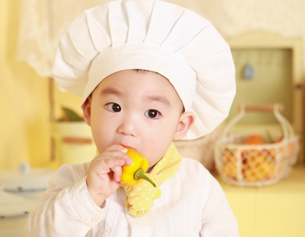 kid in chefs hat eating a pepper