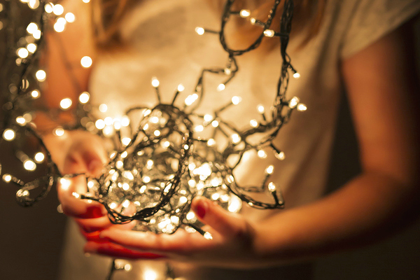 Child holding Christmas lights