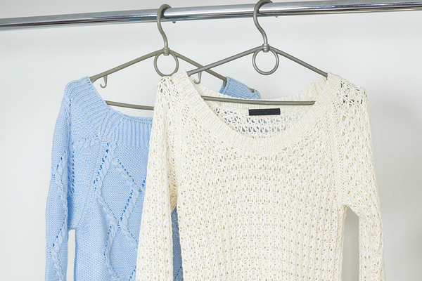 two women's sweaters hanging in closet