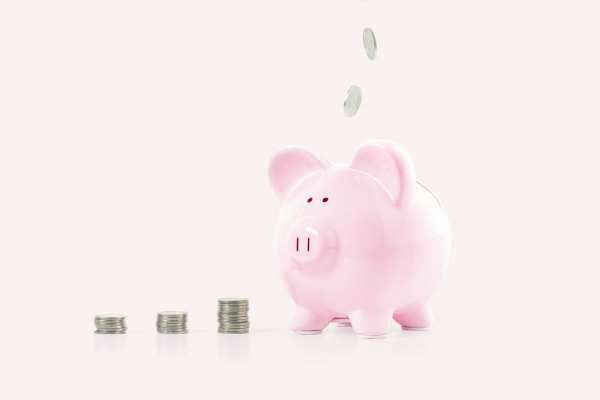 hand putting coin into piggy bank on pastel pink background