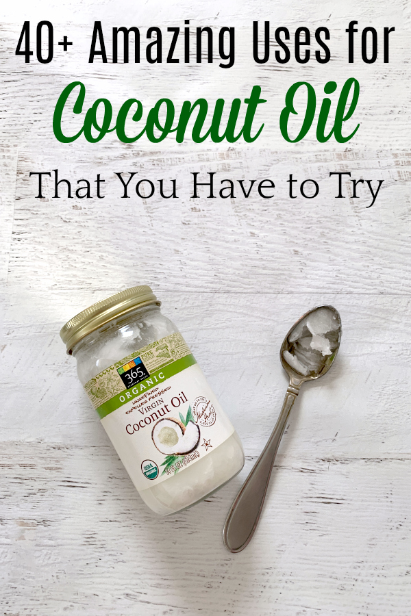 jar of coconut oil and spoon with coconut oil on white wooden background