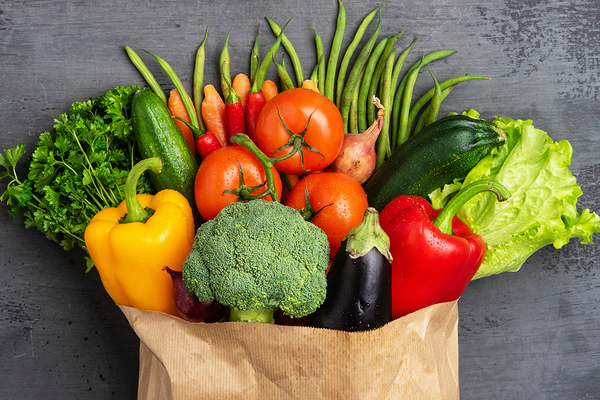 fruits and veggies in paper bag on dark background