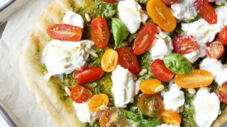 Grilled pizza with pesto, burrata, and baby tomatoes