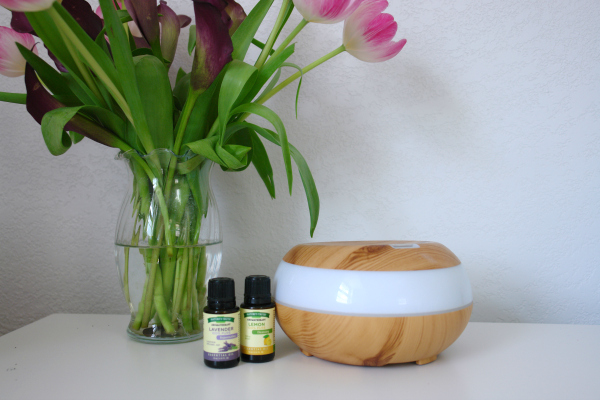 flowers, essential oils and a diffuser on table