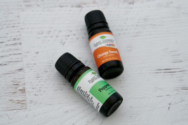 bottle of peppermint essential oil and sweet orange on white wooden background