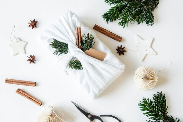 gift wrapped in white fabric with Christmas decor around it
