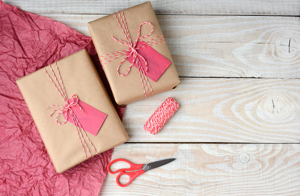 Overhead view of two Christmas presents wrapped in plain brown paper and tied with red and white string, Scissors,, spool of string and red tissue paper
