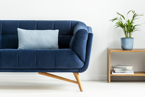 Mid-century modern chair with a blanket and a large sofa with colorful cushions in a spacious living room interior