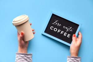 woman holding a reusable coffee cup with a sign that says zero waste coffee