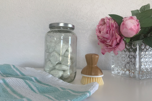 dropps tabs in glass jar with dish brush, towel, and flowers