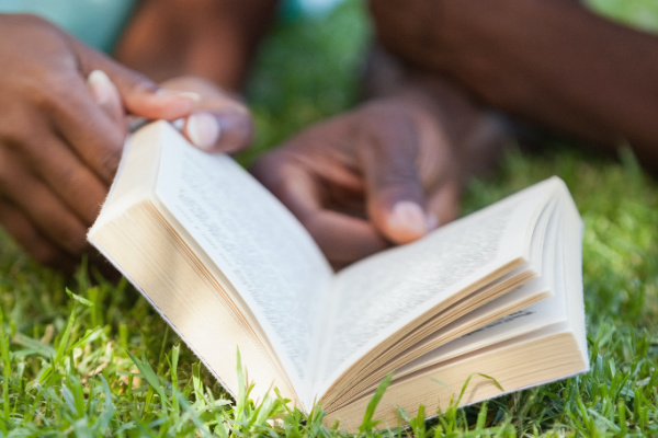 people laying in grass reading with text 20 earth day books for kids