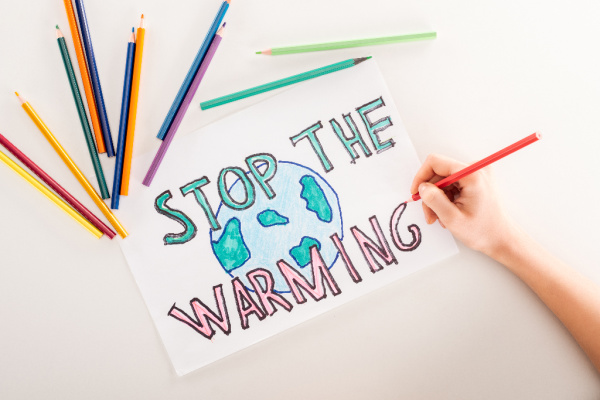 kid drawing earth and words stop the warming