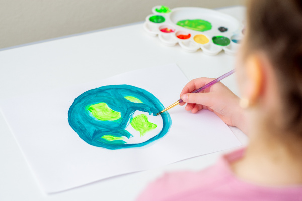 kid painting earth on white paper